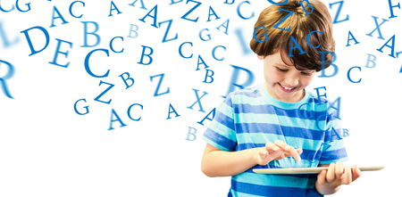 Smiling boy using digital tablet against letters Stock Photo