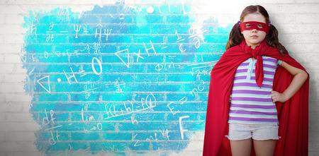 Portrait of girl in superhero costume against white wall