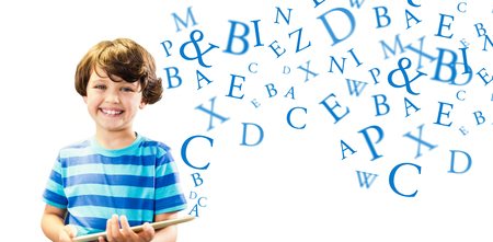 Portrait of boy with digital tablet against letters
