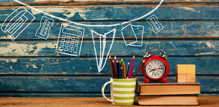 Illustration image of school supplies arranged against books with alarm clock on table