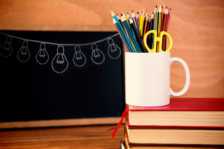 Illustration image of light bulbs arranged against desk organizer on stack of books against blackboard