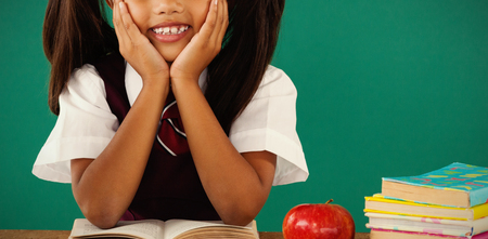 Portrait of schoolgirl reading a book against green background Stock Photo