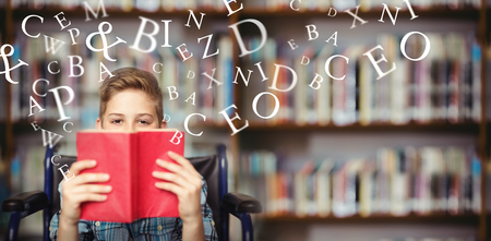 Letters on a white background against portrait of disabled schoolboy holding book in library Stock Photo