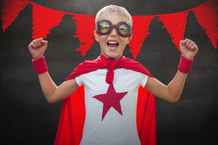 Little boy dressed as superman against black wall Stock Photo