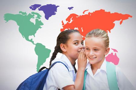 Portrait of girl whispering in friend ear against grey background