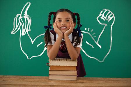 scholarship: Digital image of hand holding banana against schoolgirl leaning on books stack against chalkboard in classroom