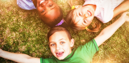 Smiling students looking at camera on elementary school grounds Stock Photo