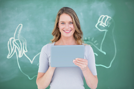 Smiling teacher using digital tablet in front of blackboard against digital image of hand holding banana
