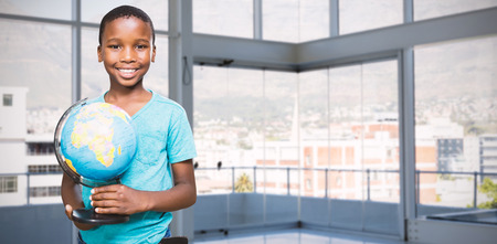 Portrait of smiling boy holding globe against buildings seen through office Stock Photo