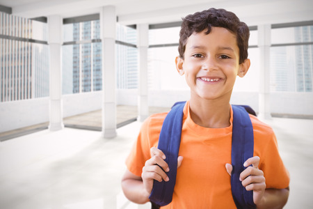navigational light: Portrait of smiling boy  against modern room overlooking city Stock Photo