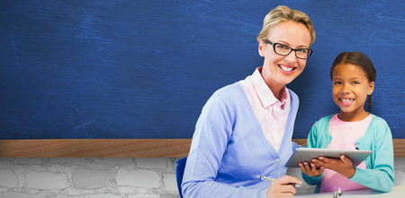 Portrait of student with teacher holding digital tablet against bueboard on wall  in school
