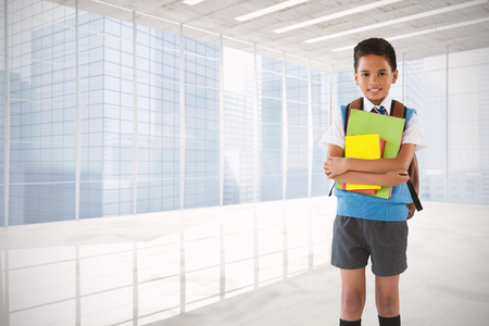 navigational light: Portrait of schoolboy holding books over white background against modern room overlooking city
