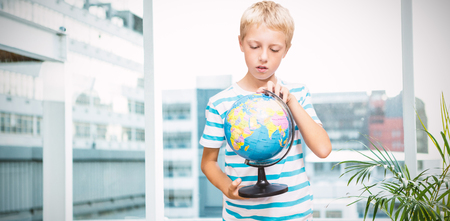 Boy looking at globe against working desk in a office Stock Photo