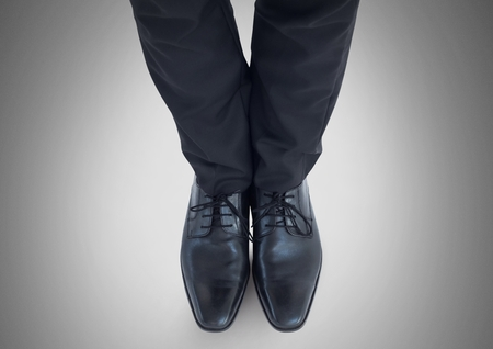 Digital composite of Businessman feet and legs with business attire and black shoes Stock Photo