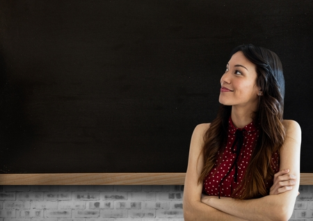 Digital composite of Woman standing in front of blackboard