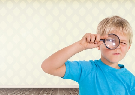 Digital composite of Boy holding magnifying glass with room background