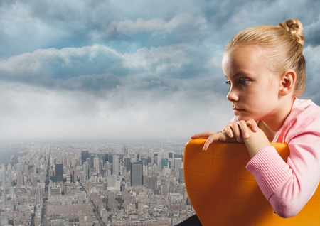 Digital composite of Girl sitting contemplative in chair over city