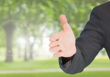 Digital composite of Hand shake arm in park Stock Photo