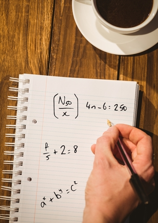 sums: Digital composite of Hand writing math sums on notepad Stock Photo