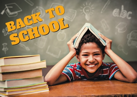 Digital composite of Education and back to school text and happy boy holding a book Stock Photo