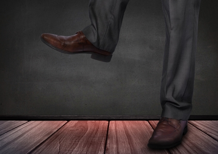 Digital composite of Mans legs and feet on wooden floor Stock Photo