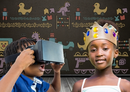 Digital composite of Boy with VR Headset and girl with crown in front of blackboard with toys graphics
