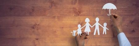 木製テーブルに対して家族の保険概念のデジタル合成