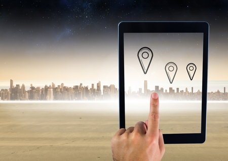 biege: Digital composite of Holding tablet and city with marker location pointers Stock Photo