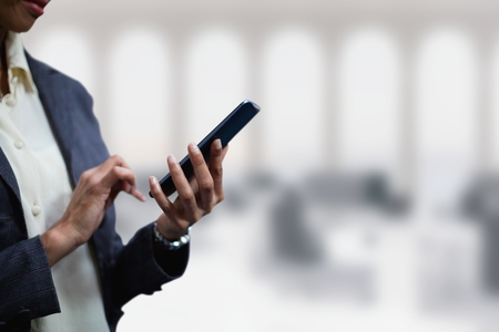 Digital composite of Business woman using a phone against office background
