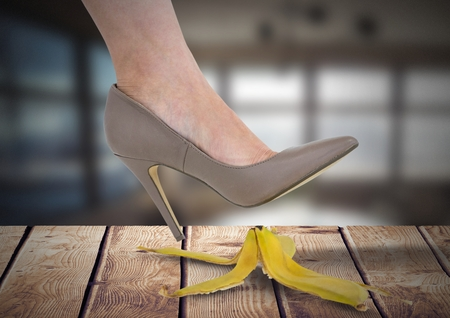 Digital composite of Womans foot about to step on banana peel and slip mistakenly on wood