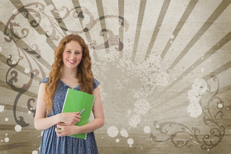 Digital composite of Happy young student woman holding a notebook against brown and white splattered background Фото со стока