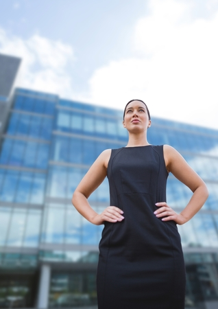 Digital composite of Business woman standing against building background Stock Photo