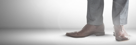 Digital composite of Businessmans feet and shoes with grey background