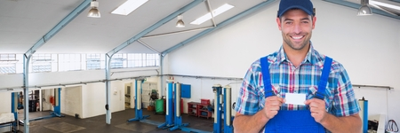 auto repair: Digital composite of Happy mechanic man holding a business card Stock Photo