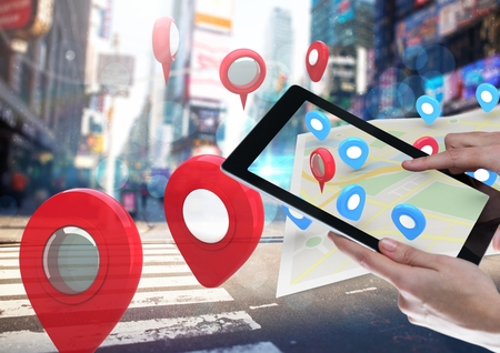 Digital composite of Holding tablet and City with  marker location pointers and map Stock Photo