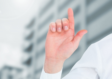 extending: Digital composite of Hand pointing up in front of buildings