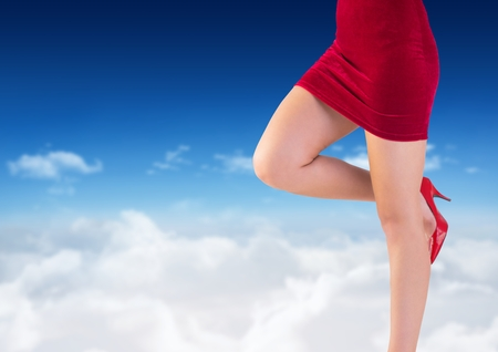 Digital composite of Sexy womans legs in red skirt and shoes in front of blue sky