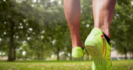 Digital composite of Athletic feet running in park Stock Photo