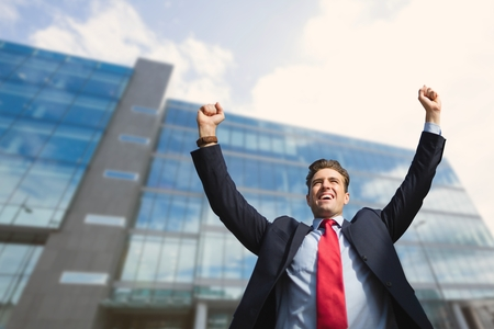 Digital composite of Excited business man standing against building background Banque d'images