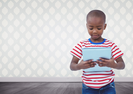 Digital composite of Boy holding tablet in blank room