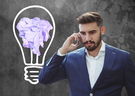 businesswear: Digital composite of Man on phone standing next to light bulb with crumpled paper ball