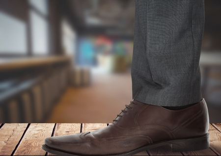 Digital composite of Businessmans foot and shoe on wood Stock Photo