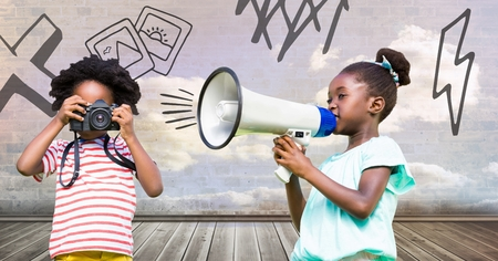 Digital composite of kids holding megaphone and camera with cloudy room background and drawings