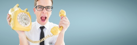 Digital composite of Angry man holding a yellow phone against blue background