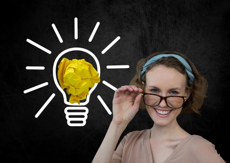 Digital composite of Woman standing next to light bulb with crumpled paper ball Stock Photo