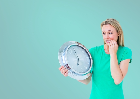 Digital composite of Woman holding clock in front of turquoise background Stock Photo