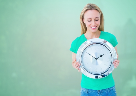 Digital composite of Woman holding clock in front of green background Stock Photo
