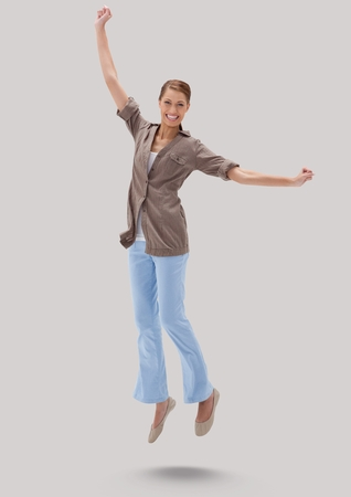 Digital composite of Full body portrait of woman jumping with grey background