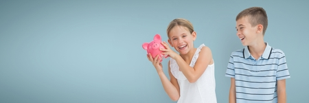 Digital composite of Happy boy and happy girl holding a piggy bank against blue background 免版税图像