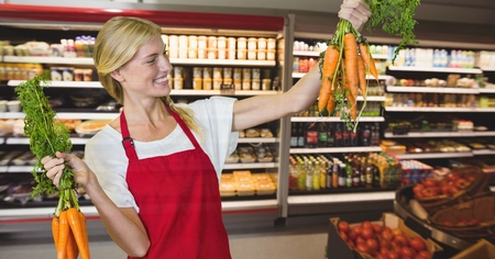 Digital composite of Happy small business woman holding carrots